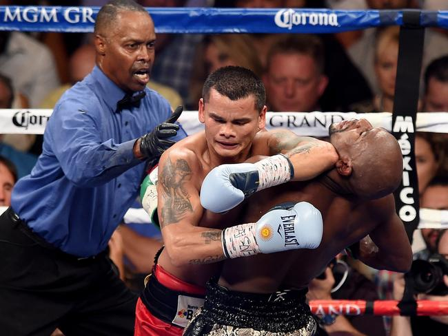 Marcos Maidana puts his left forearm in the neck of Floyd Mayweather Jr.
