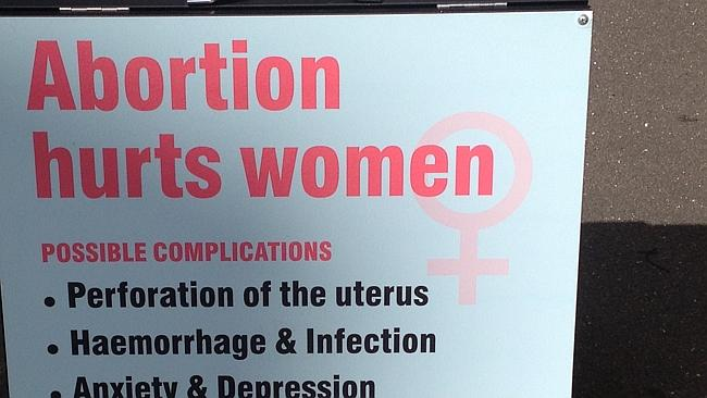 Mr Hanrahan places this sign across the road from the clinic. It also has an image of an unborn foetus which is too graphic to p