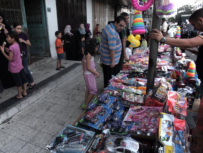 A Palestinian street vendor displays toys for sale as a 72-hour Hamas and Israel cease fire began in Gaza City. AP Photo/Khalil Hamra