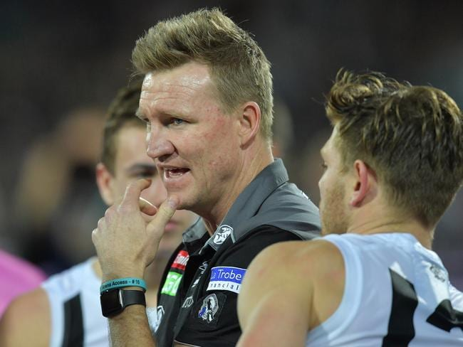 Magpies head coach Nathan Buckley hands instructions to his players.