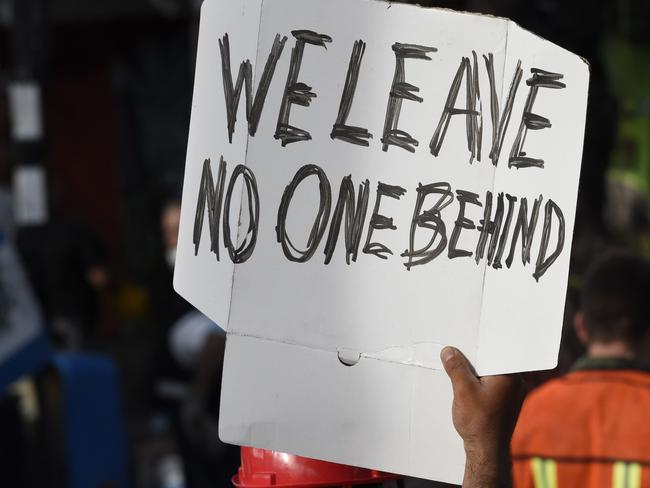 """Someone holds up a sign reading """"We leave no one behind"""" as rescue workers search for survivors in Mexico City. Picture: AFP"""