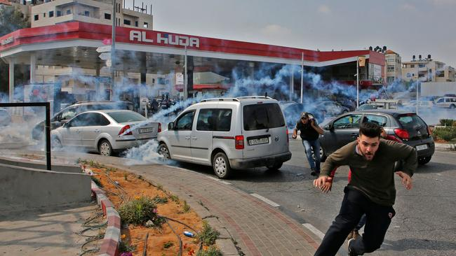 Palestinians run away from tear gas shot at them by Israeli forces during a protest in Ramallah, in the occupied West Bank. Picture: AFP