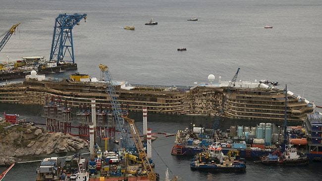 "The crippled Costa Concordia is seen after it was lifted upright on the Tuscan Island of Giglio, Italy, after a complicated, 19-hour operation to wrench it from its side where it capsized last year, with officials declaring it a ""perfect"" end to a daring and unprecedented engineering feat. (AP Photo/Andrew Medichini)"