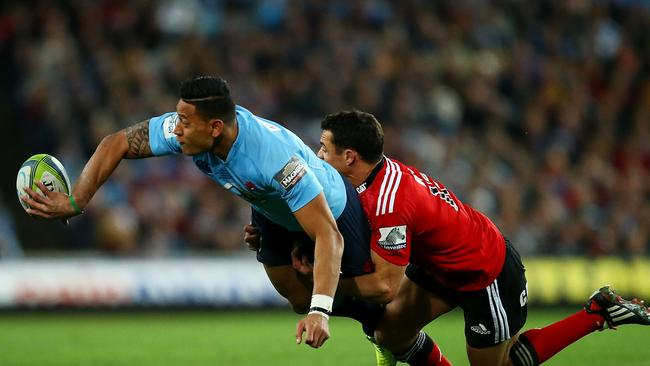 Israel Folau gets an offload away despite a tackle from Crusaders star Dan Carter.