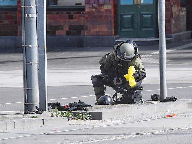 A member of the bomb squad checks a bag found at the scene. Picture: Jason Edwards