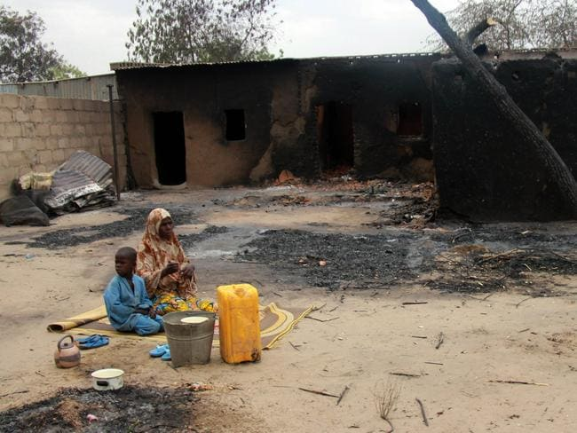 Destruction ... a family sits outside a burnt house in the remote northeast town of Baga on April 21 after two days of clashes between officers of the Joint Task Force and Boko Haram. Picture: AFP