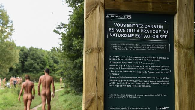 "Two naked persons walk past a sign reading ""you are entering a space where the practise of naturism is authorised"" at the Bois de Vincennes park in Paris."