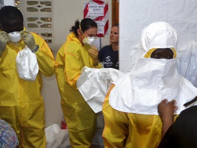 Charity workers put on protective clothing to treat patients with the illness. Pic: AFP, Zoom Dosso