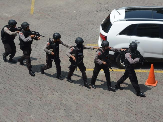Indonesian police commandos ... arrive near a damaged Starbucks coffee shop. Picture: AFP