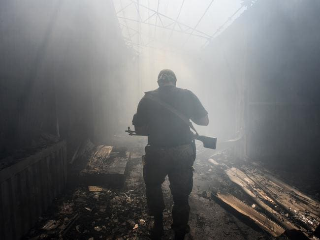 Shady origins ... A Pro-Russian rebel walks in a passage at a market damaged by shelling in Petrovskiy district in the town of Donetsk, eastern Ukraine. Source: AP