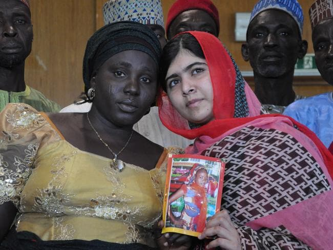 Yousafzai holds a picture of kidnapped schoolgirl Sarah Samuel with her mother Rebecca during a visit to Abuja, Nigeria. Picture: Olamikan Gbemiga