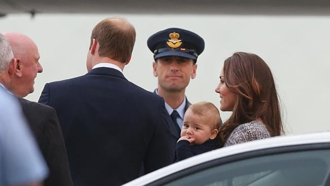 Prince William and Catherine, the Duchess of Cambridge, holding Prince George have a quick chat with officials at Sydney Airport before boarding a flight to New Zealand. Picture: Cameron Richardson