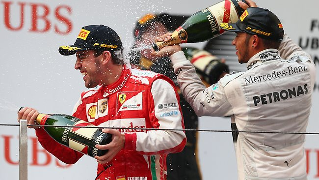 Race winner Fernando Alonso of Spain celebrates on the podium with third-placed Lewis Hamilton.