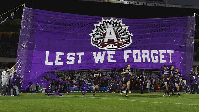 Storm players run through the banner before the inaugural Anzac Day clash against the Warriors.