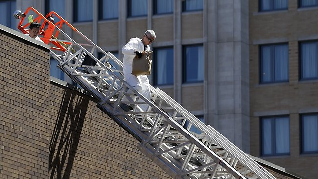 An FBI investigator walks down a fire truck escalator with a bag from a building at the corner of Boylston Street and Fairfield Street , Wednesday, April 17, 2013, in Boston. Investigators in white jumpsuits fanned out across the streets, rooftops and awnings around the blast site in search of clues on Wednesday. (AP Photo/Julio Cortez)