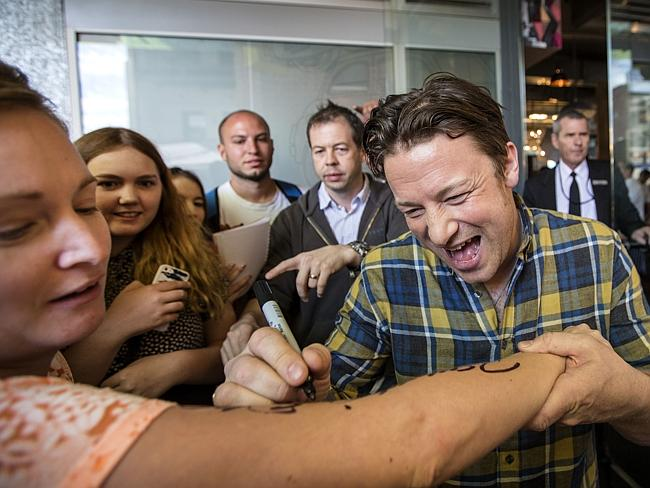 A major celebrity ... Jamie Oliver signs the arm of a fan at his Perth restaurant.