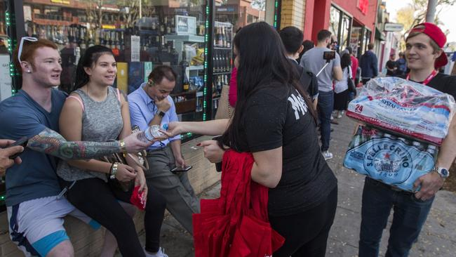 Employees give water to people waiting in line to get into MedMen, one of two Los Angeles pot shops that began selling recreational marijuana under new Californian law. Picture: David McNew/Getty/AFP