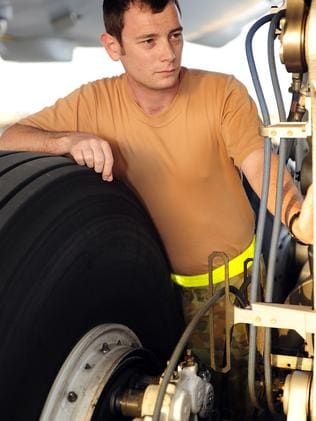 Leading Aircraftman Cameron Newell inspects the landing gear on a Multi Role Tanker Transport at Australia's logistic base in the Middle East.