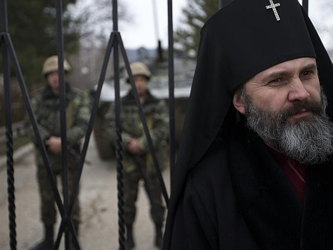 Human shield: A Ukrainian Orthodox Archbishop guards the gateto a Ukrainian military base in the village of Perevalne, outside of Simferopol, Ukraine. Picture: AP