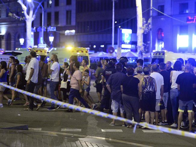 People gather to leave the cordoned off area after the incident in Barcelona.