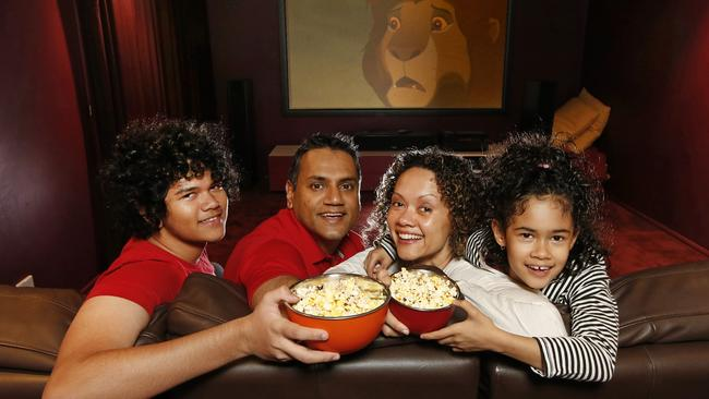 Eddie and Lise Prasad, sit down to watch a movie with their children William, 14, and Tiana, 7, in their home theatre room. Picture: David Caird