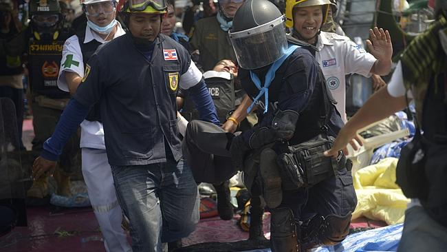 Two protesters die ... A police officer is carried to an ambulance after he was shot in t