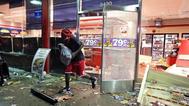 Several car windows were smashed and stores were looted after the vigil. Picture: AP