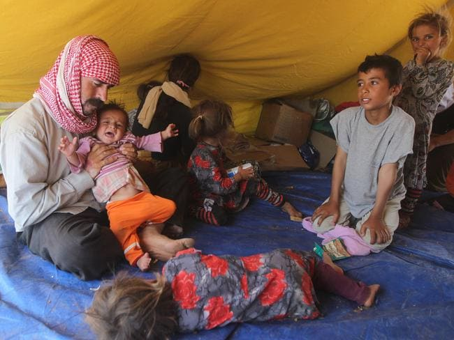 Escaped ... Yazidi refugees sit inside a tent at the Newroz camp in Hasaka province, north eastern Syria.