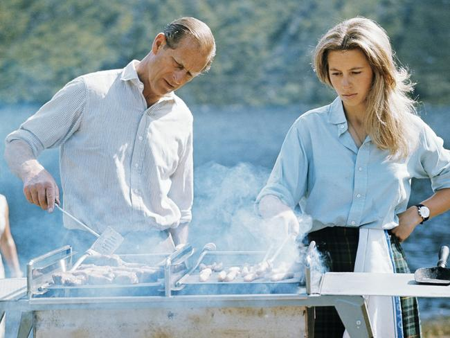 A rare glimpse into royal life: Prince Philip and Princess Anne barbecuing at Balmoral Castle in 1972. Picture: Lichfield/Getty.