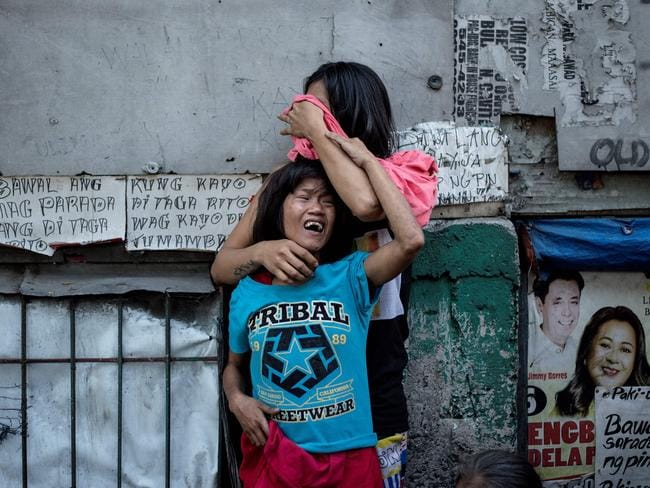 Analyn Roxas, 26, and her sister cry after her partner, Valien Mendoza, a suspected drug dealer, was gunned down by unidentified assailants in Manila on March 7. Picture: AFP/Noel Celis