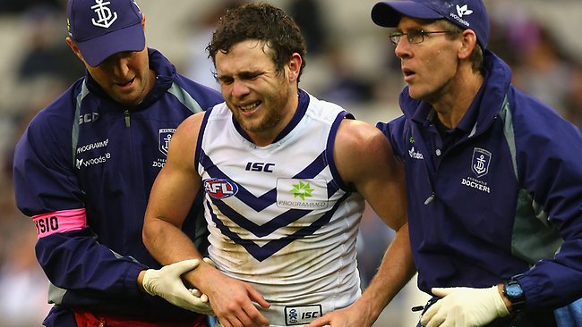 MELBOURNE, AUSTRALIA - AUGUST 18: Hayden Ballantyne of the Dockers is helped off the ground by trainers during the round 21 AFL match between the Melbourne Demons and the Fremantle Dockers at Melbourne Cricket Ground on August 18, 2013 in Melbourne, Australia. (Photo by Quinn Rooney/Getty Images)