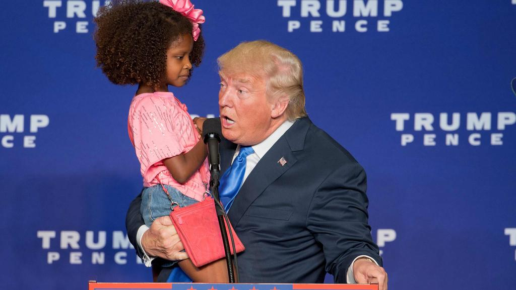 Republican presidential nominee Donald Trump holds a little girl who he repeatedly called beautiful during a rally in Wisconsin. Picture: Tasos Katopodis/AFP