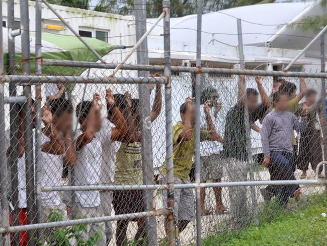 Asylum seekers staring at media from behind a fence at the Oscar compound in the Manus Island detention centre in 2014. Picture: AAP