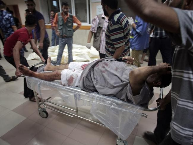 More blood shed ... Palestinians wheel an injured man next to bodies of six members of the Gharabli family who were killed in an Israeli strike, at the Shifa hospital in Gaza City.