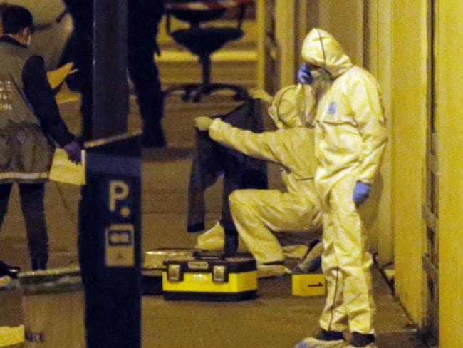 French forensic experts examine evidence outside the Paris offices where the deadly attack occurred. Picture: AP Photo/Francois Mori.