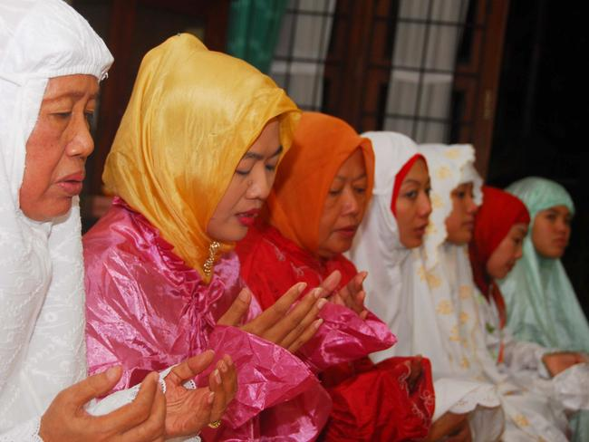 Mother of Indonesian presidential candidate Joko Widodo, Sudjiatmi (L) and relatives pray for Widodo at her home in Solo Pic: AFP/ANWAR MUSTAFA