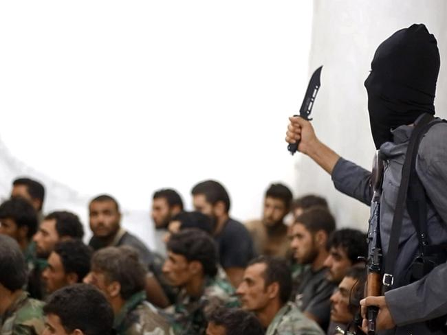 A fighter from the Islamic State group, armed with a knife and an automatic weapon, next to captured Syrian army soldiers and officers after the battle for the Tabqa air base, in Raqqa, Syria. Picture: AP /Raqqa Media Centre of the Islamic State group)