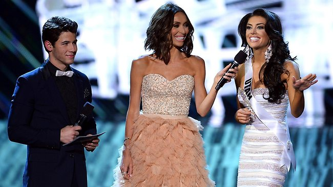 Recording artist and host Nick Jonas and television personality and host Giuliana Rancic look on as Miss Utah USA Marissa Powell answers a question from a judge during the interview portion of the 2013 Miss USA pageant.
