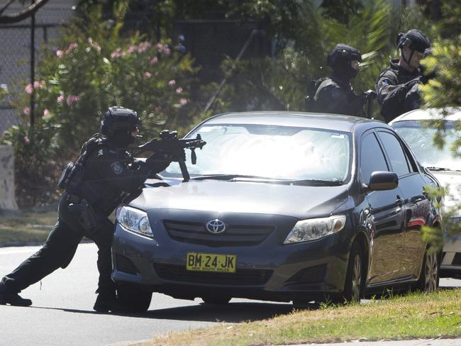Armed police take cover behind cars. Picture: Melvyn Knipe