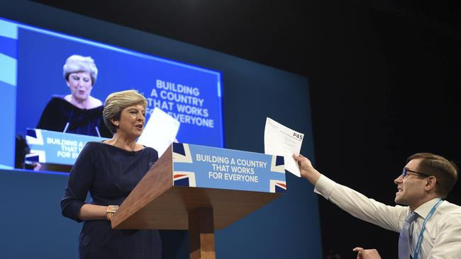 Comedian Simon Brodkin, also known as Lee Nelson confronts British Prime Minister Theresa May during her keynote speech.