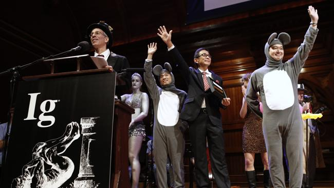 Master of ceremonies Marc Abrahams, left, introduces the winners of the Medicine Prize, Xiangyuan Jin, right mouse, of China, Masanori Niimi of Japan and Masateru Uchiyama of Japan during the annual Ig Nobel prize ceremony at Harvard University. They won for assessing the effect of listening to opera on heart transplant patients who are mice. (AP Photo/Winslow Townson)