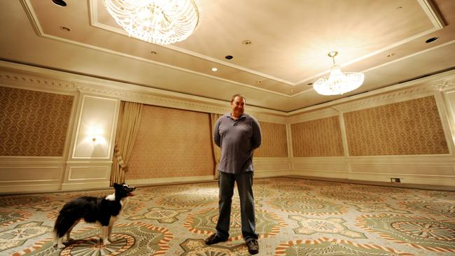 Caretaker David Churchill and his dog Lucy in the grand ballroom of the hotel in 2011. Picture: Dan Himbrechts