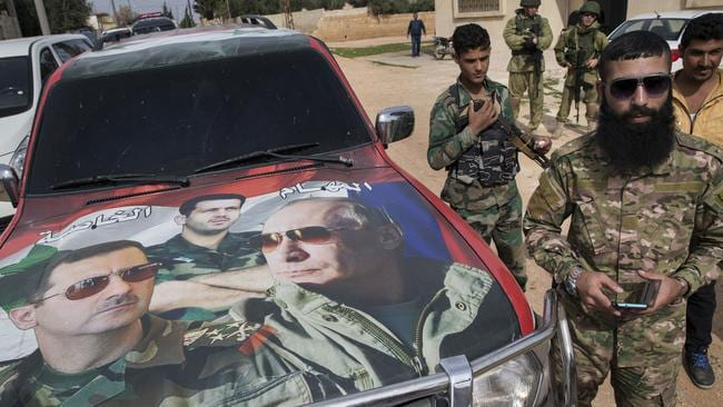Syrian and Russian soldiers stand near a car covered by images of Putin and Syrian President Bashar Assad. Picture: AP Photo/Pavel Golovkin