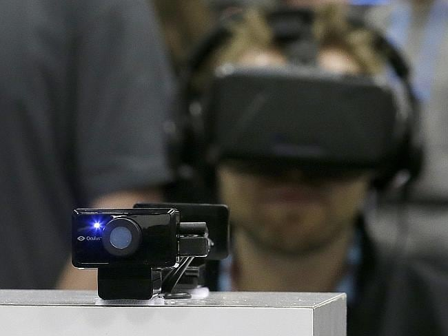 The Oculus virtual reality camera is shown as a man tries on the headset at the Game Developers Conference.