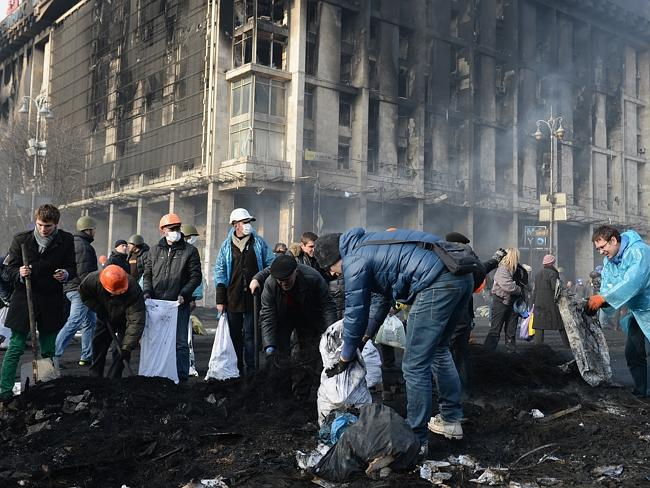 A city destroyed ... anti-government protesters clear debris following continued clashes with police in Independence Square. Picture: Jeff J Mitchell/Getty Images
