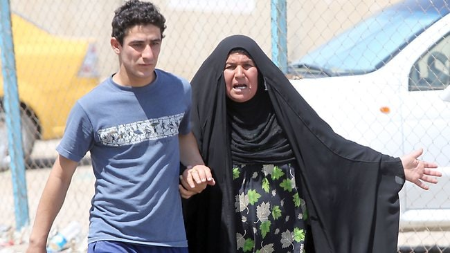 An Iraqi women shouts as she is escorted by one of her sons after his brother was killed in a suicide bombing on a Shiite Muslim mosque in Baghdad.