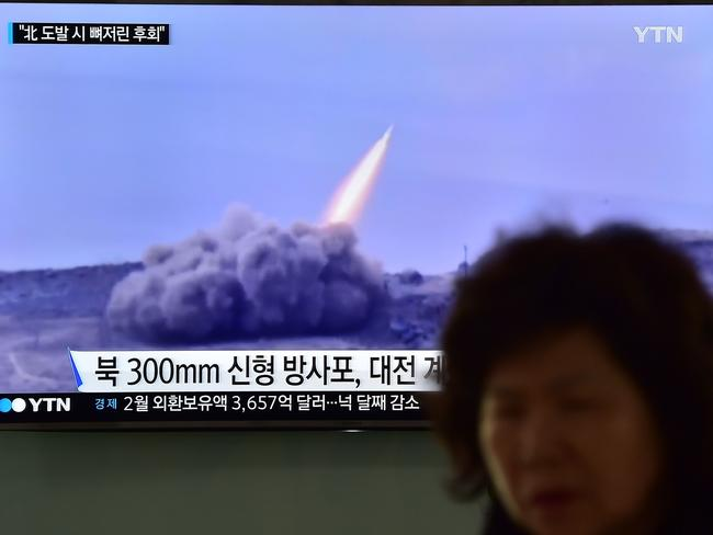 A woman walks past a public television screen showing a North Korean missile. North Korean leader Kim Jong-un has ordered its nuclear arsenal readied for pre-emptive use at anytime. Picture: AFP/Jung Yeon-Je