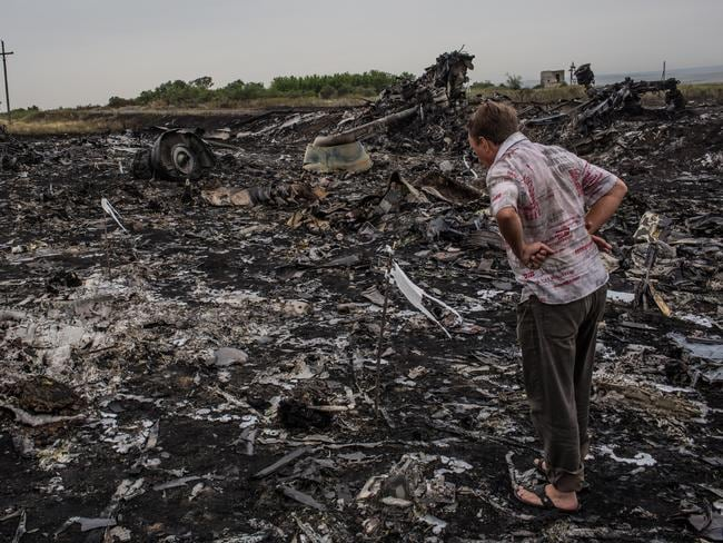 A man inspects the debris from the Malaysia Airlines plane crash at Grabovka, Ukraine. Picture: Brendan Hoffman/Getty Images