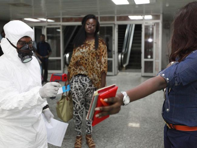 A passenger holds personal possessions as a Nigerian port health official uses a thermometer on her at the arrivals hall of Murtala Muhammed International Airport in Lagos, Nigeria.