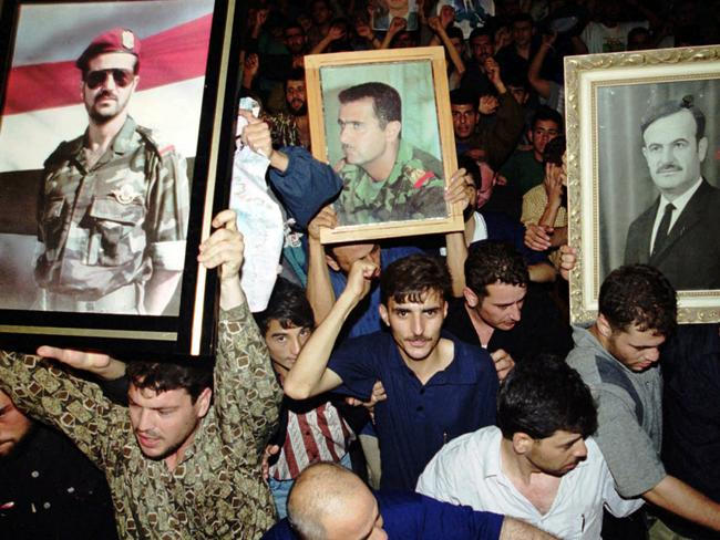 Syrians hold portraits of President Hafez Assad (right) son Bashar (centre) and son Bassel, following the President's death in 2000.